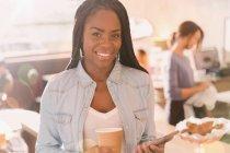 Porträt lächelnde afrikanische Frau mit Handy und trinken Kaffee im café — Stockfoto