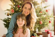 Portrait smiling mother and daughter in front of Christmas tree — Stock Photo