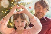 Porträt, Lächeln, Vater und Tochter bilden Herzform Weihnachtsbaum — Stockfoto