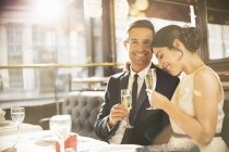 Well-dressed couple drinking champagne in restaurant — Stock Photo