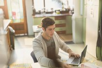 Young man college student studying at laptop in kitchen — Stock Photo