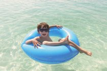 Portrait smiling boy in sunglasses floating in blue inflatable ring in ocean — Stock Photo