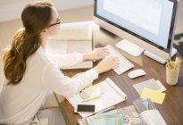 Дизайнер интерьера работает за компьютером в домашнем офисе — стоковое фото
