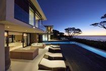 Patio de escaparate de la casa de lujo moderno con piscina iluminada al atardecer - foto de stock