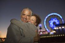 Portrait de couple caresses à l'extérieur du parc d'attractions de nuit — Photo de stock