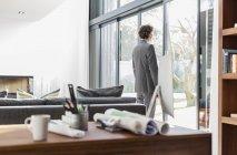 Arquitecto masculino mirando por la ventana del patio en la oficina en casa - foto de stock