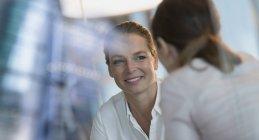 Smiling businesswoman écoute de collègue, flou fond — Photo de stock