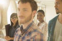 Retrato de sonriente empresaria informal con compañeros de trabajo - foto de stock