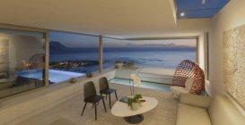 Illuminato moderno, casa di lusso vetrina soggiorno e piscina con vista sull'oceano crepuscolo — Foto stock