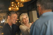 Smiling friends talking in restaurant — Stock Photo