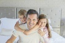 Pai e filhos abraçando no quarto — Fotografia de Stock