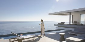 Woman walking on sunny, modern, luxury home showcase exterior patio with ocean view — Stock Photo