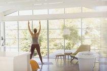 Женщина, практикующая йогу в горной позе в роскошной спальне отеля — стоковое фото