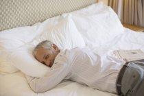 Uomo d'affari che posa sul letto nella camera d'albergo — Foto stock