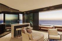 Moderno salón y bar con vistas al océano al atardecer - foto de stock