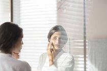 Woman applying moisturizer to cheek in bathroom mirror — Stock Photo