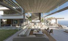 Солнечный, открытые современные, роскошные дома витрина интерьер гостиной с видом на внутренний двор и океан — стоковое фото
