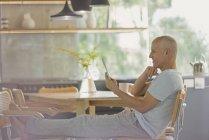 Reifer Mann entspannt sich mit digitalem Tablet und Füßen am Esstisch — Stockfoto