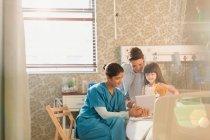 Krankenschwester zeigt Patientin und Mutter digitales Tablet im Krankenhauszimmer — Stockfoto