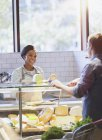 Lächelnde junge Frau hilft Kundin an Käsetheke im Lebensmittelmarkt — Stockfoto