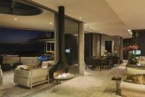 Современные дома Витрина освещенная роскошный интерьер с подвесной камин — стоковое фото