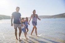 Семья, вместе ходить вдоль берега — стоковое фото