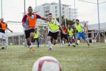 Calcio con giocatori di calcio che corre avanti — Foto stock