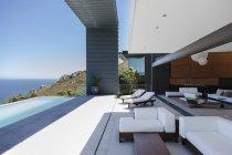 Sillas de salón y piscina infinita en un moderno patio con vistas al océano - foto de stock
