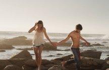 Молодая пара, взявшись за руки и ходить на морские скалы — стоковое фото