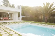 Luxury swimming pool surrounded by paver stones — Stock Photo