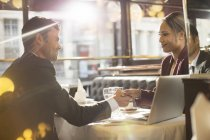 Business people shaking hands in restaurant — Stock Photo