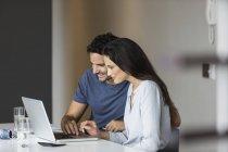 Кавказская пара за столом дома с ноутбуком — стоковое фото