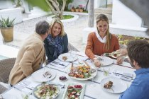 Couples drinking white wine and and eating lunch at patio table — Stock Photo