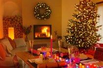 Ambiente mesa de la cena de Navidad en la sala de estar con chimenea y árbol de Navidad - foto de stock
