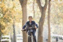 Souriant garçon vélo équitation dans le parc — Photo de stock