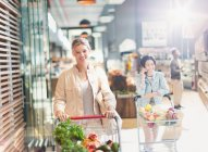 Porträt lächelnde junge Frau mit Einkaufswagen im Supermarkt Markt — Stockfoto