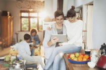 Smiling young couple using digital tablet in kitchen — Stockfoto