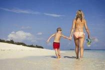 Madre e figlio a piedi sulla spiaggia tropicale soleggiata — Foto stock
