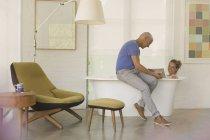 Зрелый мужчина показывает женщинам цифровые таблетки в ванне — стоковое фото