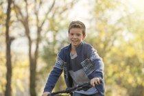 Caucasian boy at bike riding in autumn park — Stock Photo
