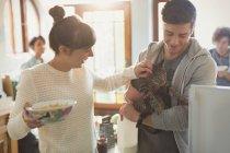 Jeune couple chat caresser dans la cuisine — Photo de stock