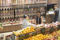 Young women grocery shopping, browsing produce in market — Stock Photo