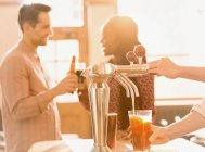 Couple drinking beer behind bartender pouring beer at beer tap in bar — Stock Photo