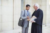 Giudice e avvocato che esaminano i documenti in tribunale — Foto stock