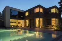 Modern house and swimming pool illuminated at dusk — Stock Photo