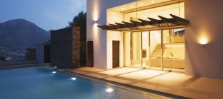 Illuminated modern house overlooking swimming pool — Stock Photo