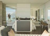 Reflexão do casal olhando vista mar sol da varanda de quarto moderno luxo casa vitrine — Fotografia de Stock