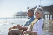 Portrait of senior couple relaxing in lawn chairs on beach — Stock Photo
