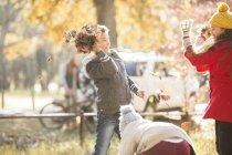 Ragazzo che lancia foglie autunnali alla ragazza nel parco — Foto stock
