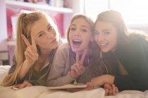 Portrait teenage girls gesturing peace sign — Stock Photo
